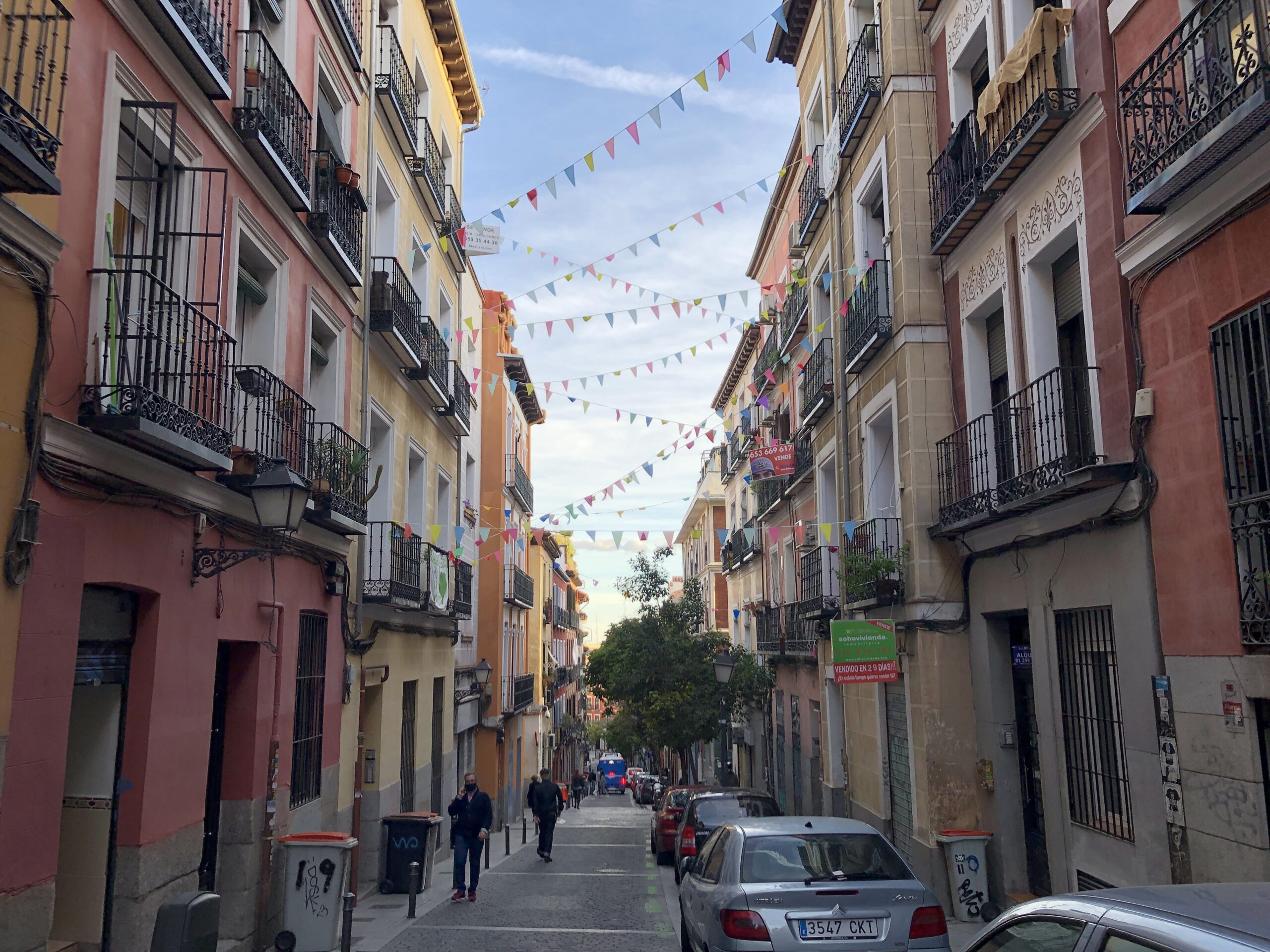 Multicoloured flags span a street with colourful facades in the south of Madrid.