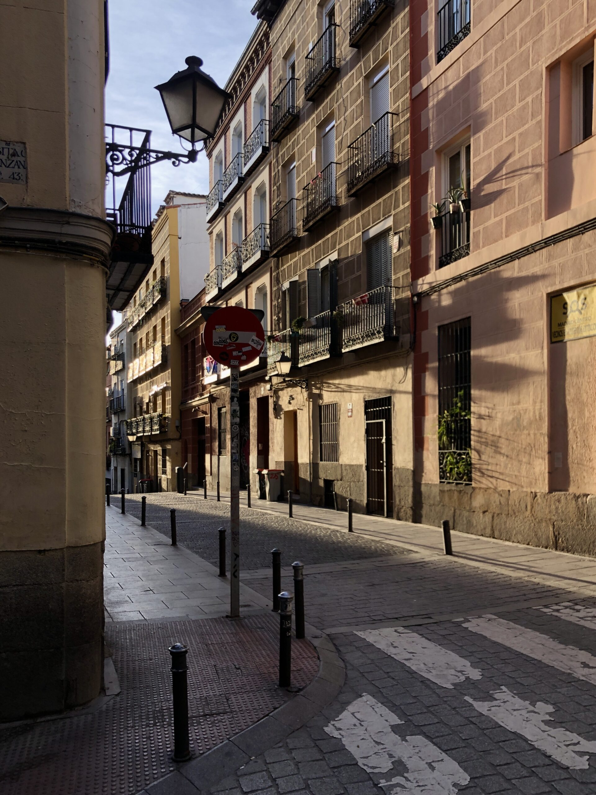 The evening sunlight casts long shadows on the facades of a street in Madrid.